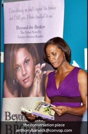 Sharisse at book reading with large stand alone banner.